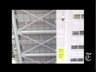 Alain Robert climbs the NY Times building to protest about global warming for the Solution is Simple campaign